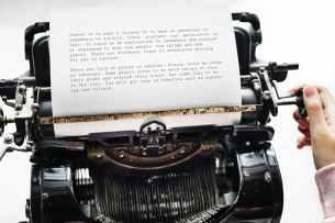 person holding black typewriter